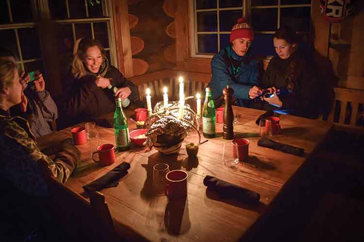 A group gathered around a candle lit table.