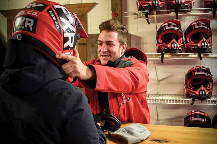 Rider getting fitted with a helmet for a snowmobile tour.