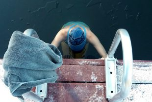 A swimmer enters the cold waters of a Whistler lake, edging down a metal stairs and breaking the ice.