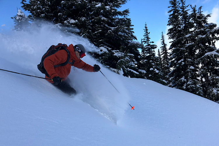 Heli-touring guide skiing in powder
