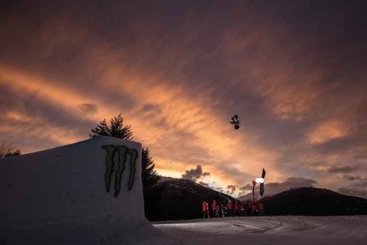 snowboarder going off of a sunset jump