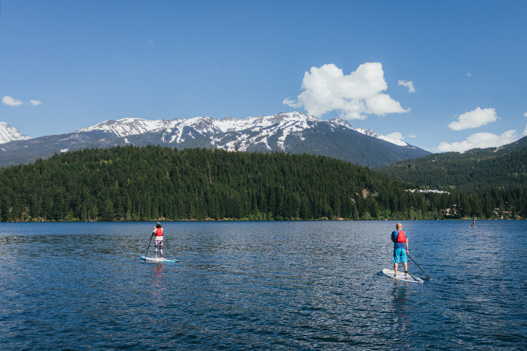 Two people paddleboarding across Alta Lake in Whistler