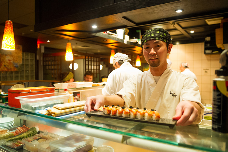 A Sushi Chef serving a roll at Sushi Village in Whistler