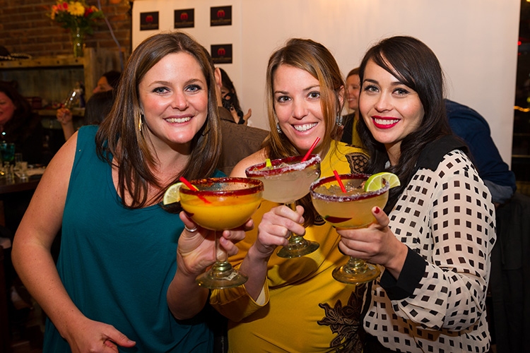 Three women holding margaritas at the Mexican Corner
