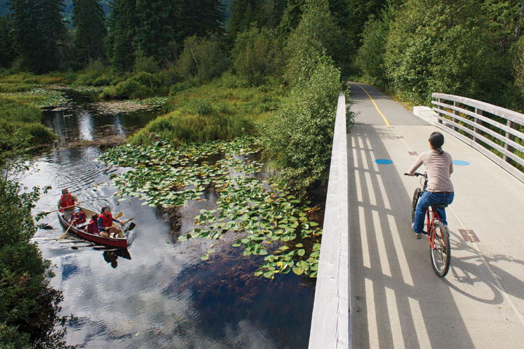 A family canoes down the River of Golden Dreams as a biker crosses the bridge above.