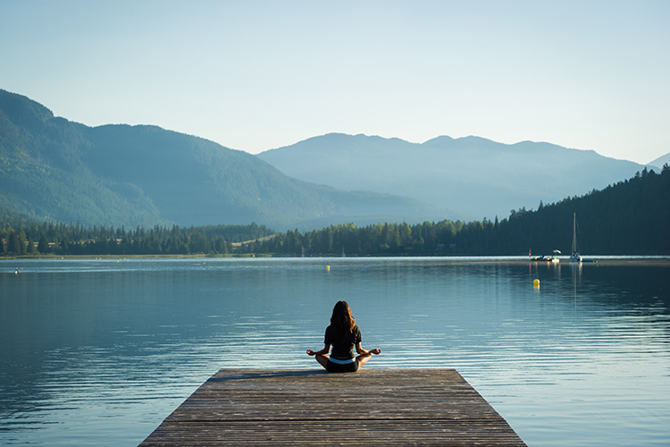 Woman meditating at a lake in Whistler