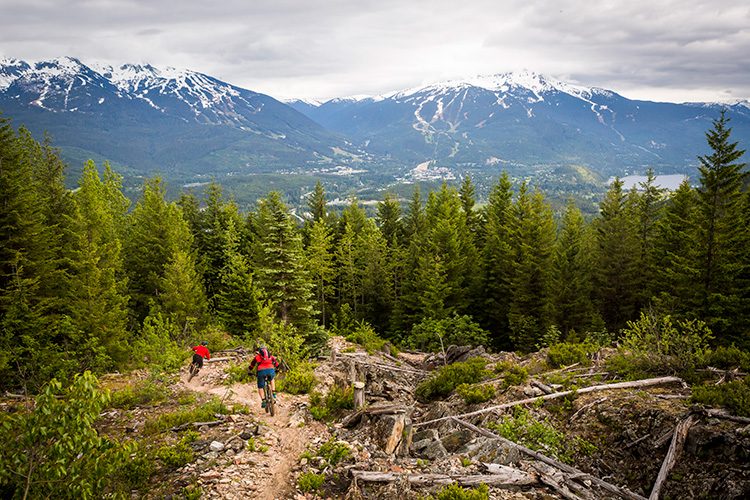 Mountain bikers riding towards Whistler and Blackcomb Mountains