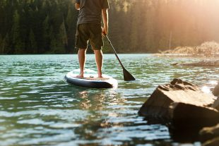 Paddleboarder leaving the shore of Cheakamus Lake