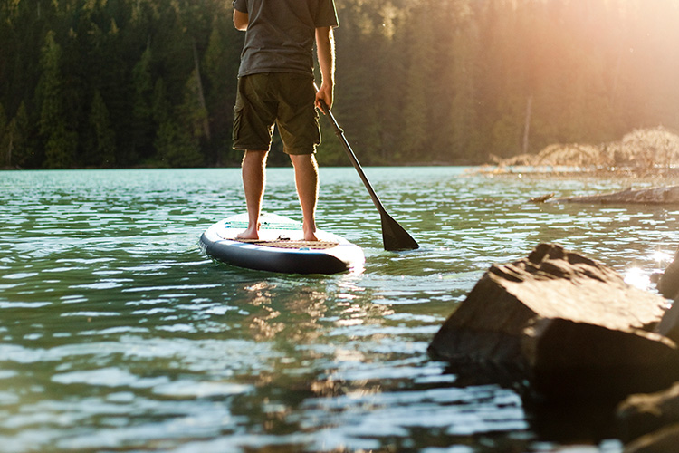 Paddleboarder leaving the shore of Cheakamus Lake