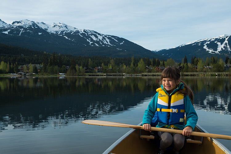 Kid paddling a canoe on a lake in Whistler