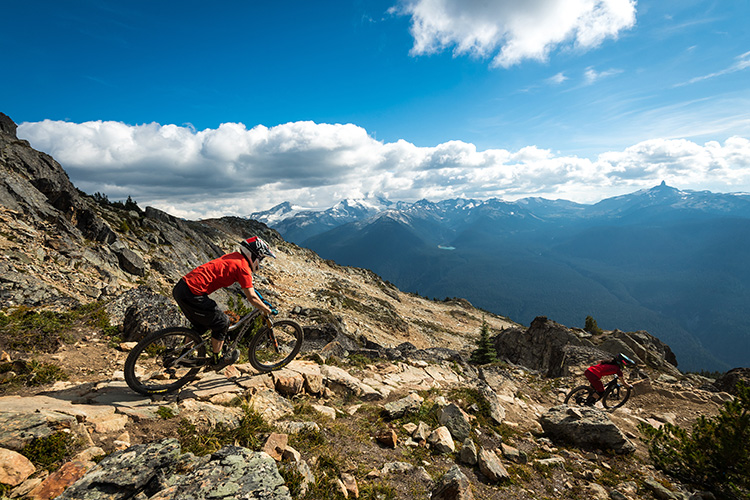Two bikers on the Top Of The World trail in Whistler