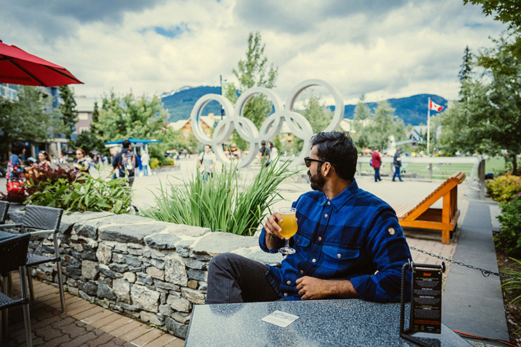 Person enjoying a beer in front of the Olympic Rings