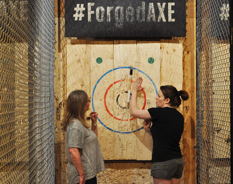 Instructor helping guest at Forged Axe Throwing