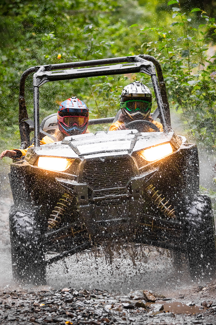 Guests driving RZR through mud