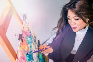 A woman paints on a canvas.