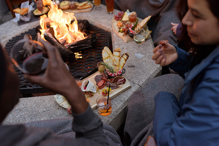People eating around a firepit in Whistler