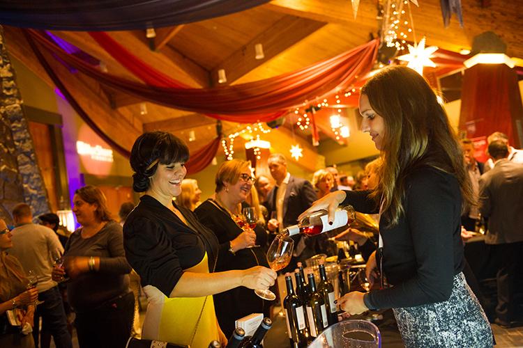 Women pouring a glass of wine at Cornucopia