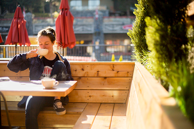 Person on sunny patio drinking coffee in Whistler