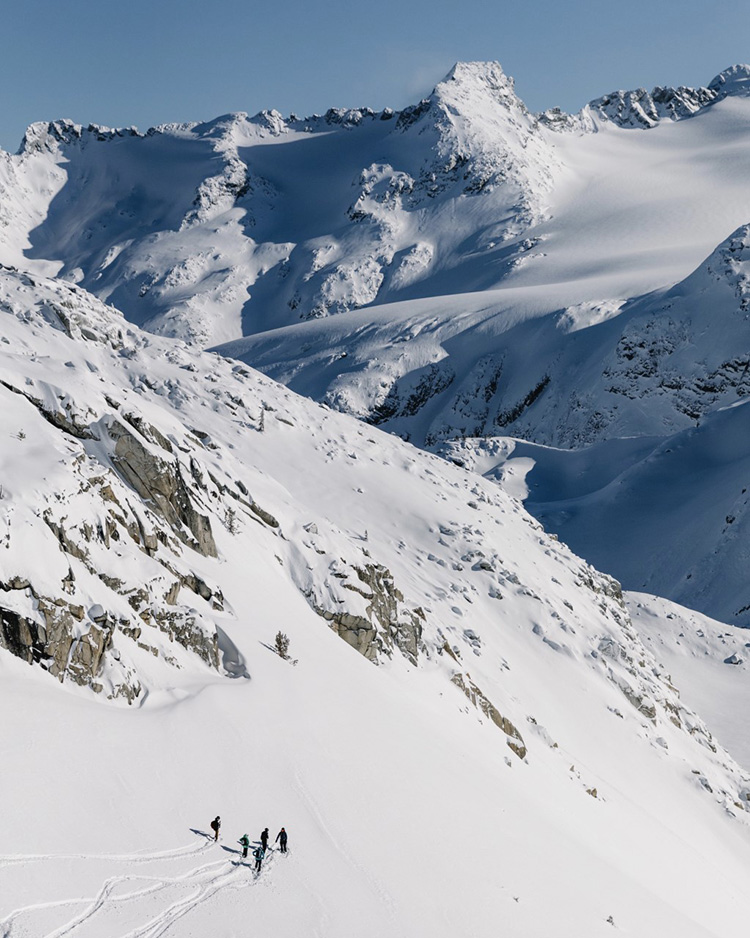 Backcountry skiers below a ridge taking in the views in Whistler