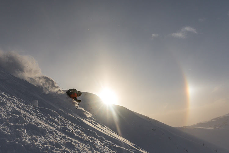 Skiier in front of a peak with a sun dog in the background
