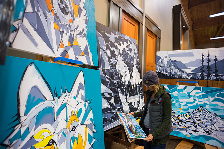 Person looking a big, brigt landscape paintings at the Whistler Artisan Market