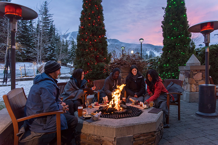 Friends around a fire on a patio in Whistler