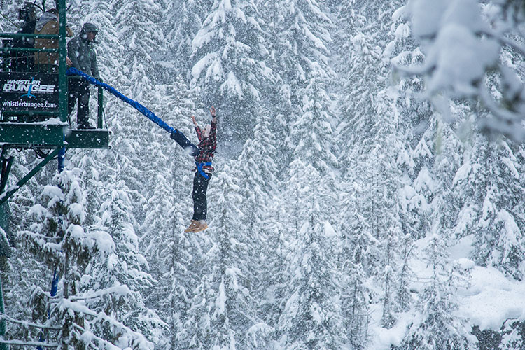 A man jumps backwards off the bridge in the snow at Whistler Bungee.