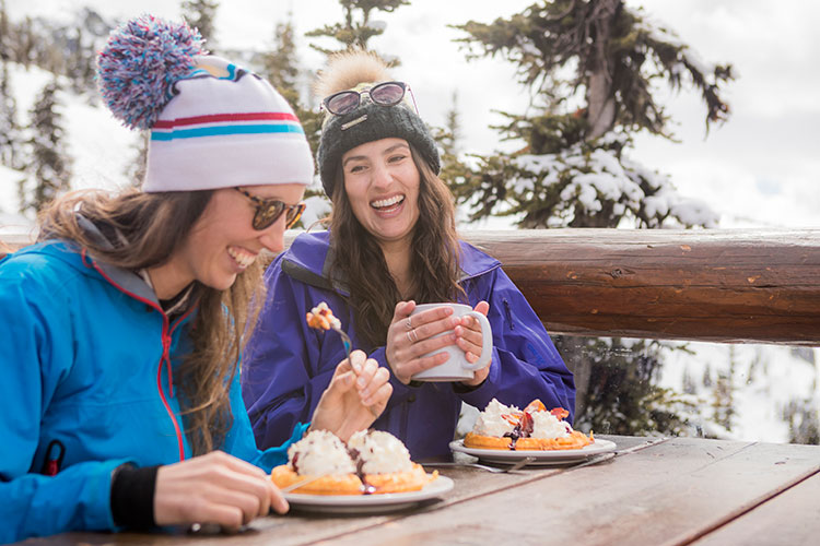 Two girls eat waffles at the Crystal Hut on Whistler Mountain.