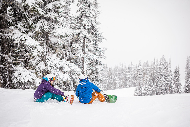 Snowboarders sit in the snow on Whistler Blackcomb.