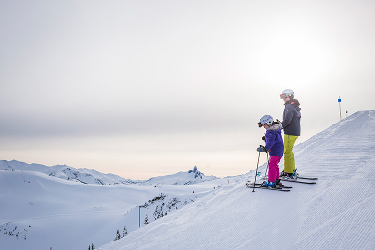 Parent and child looking down a slope getting ready to ski