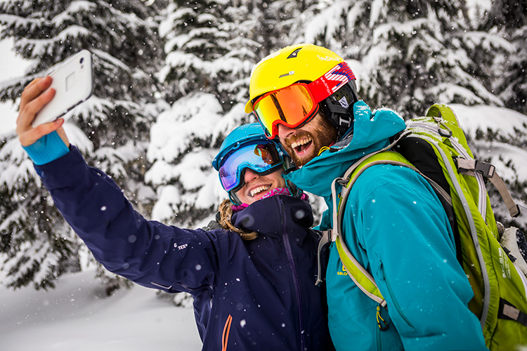 A couple taking a selfie in while snowboarding in Whistler