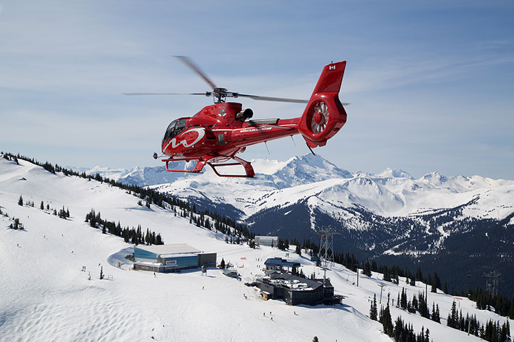 A red helicopter hovers over Blackcomb Mountain in Whistler.