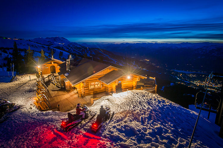 Snowmobilers pull up to the Crystal Hut on Blackcomb Mountain for a fondue dinner.
