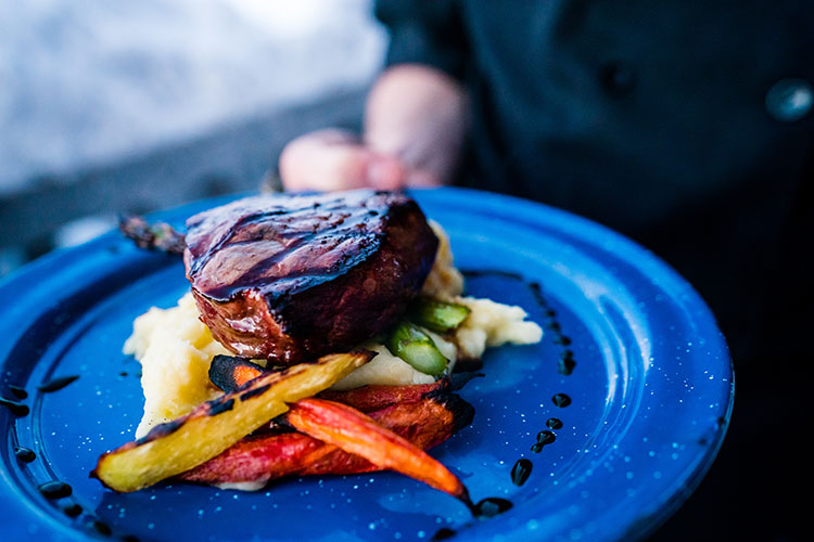 A steak is served at Canadian Wilderness Adventure's snowmobile tour to a backcountry cabin.