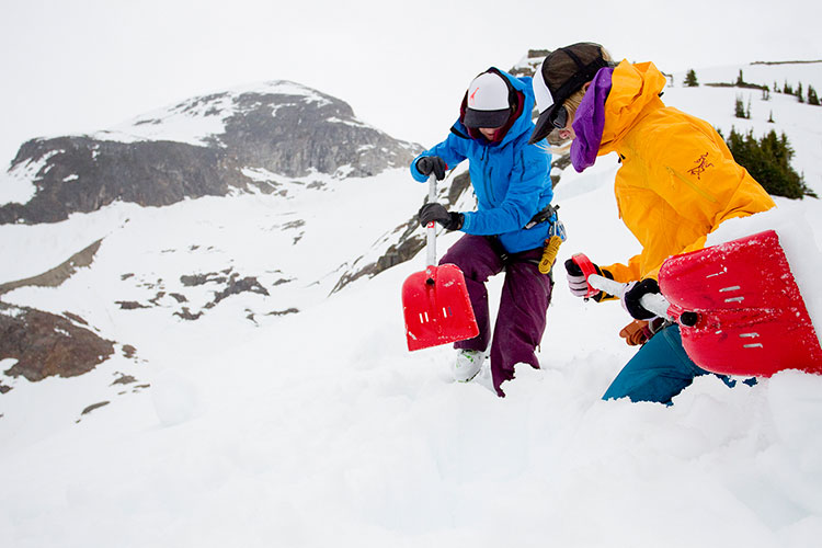Two guides shovel snow in the backcountry of Whistler.