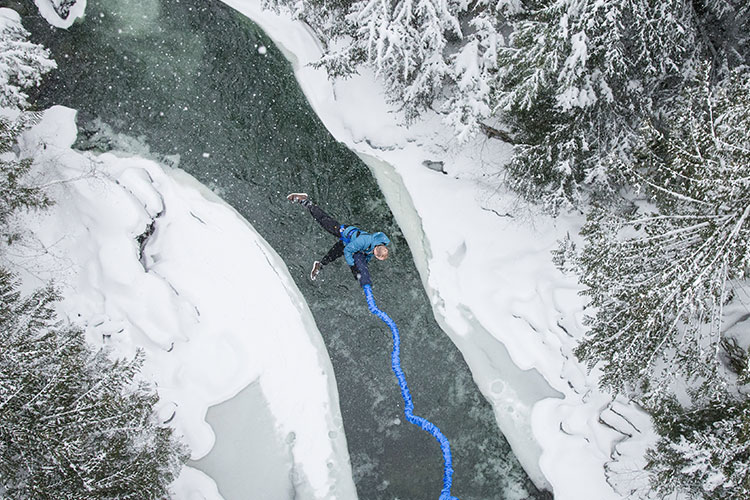 A man bungee jumps in Whistler over the Cheakmus River as snow falls.