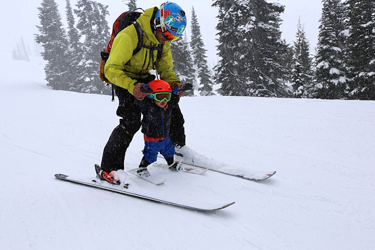 A father and his toddler ski on Whistler Mountain
