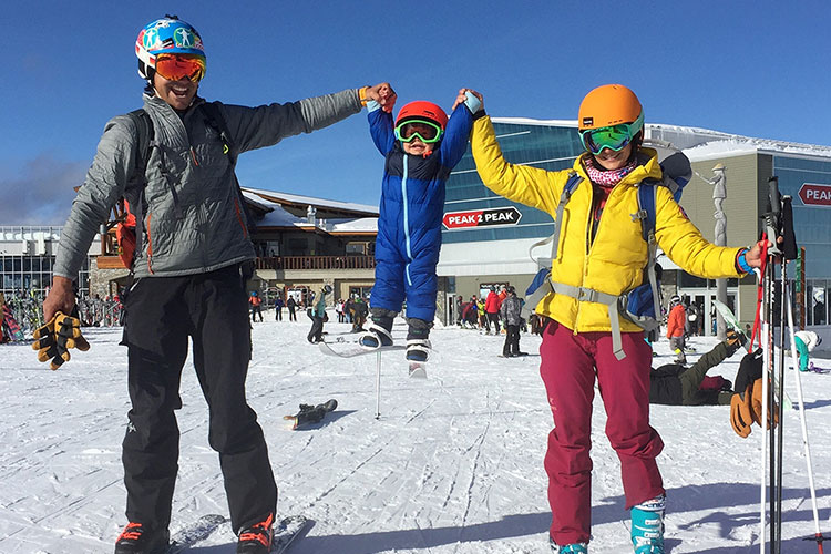 A family hold up their child between them celebrating after his first ski day on Whistler Mountain.