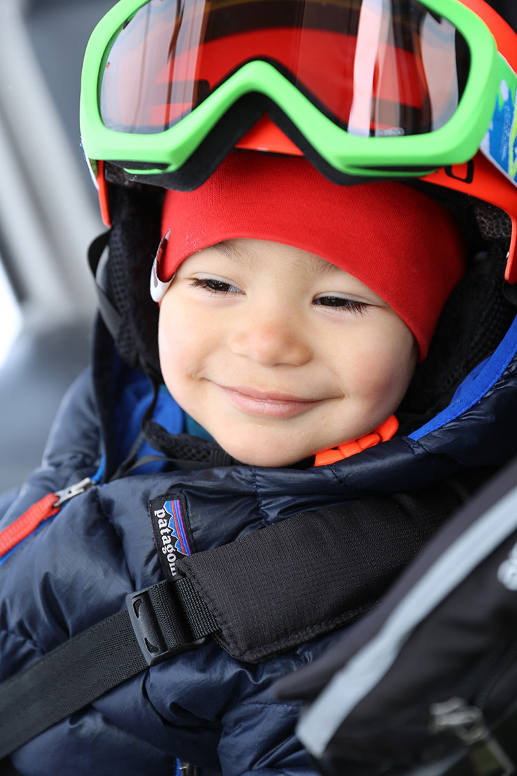 A little boy smiles after his first ski day in Whistler.