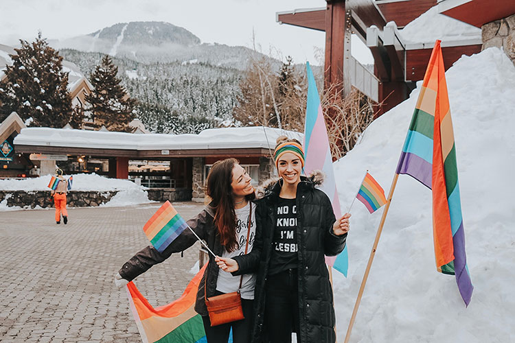 Two women hold rainbow flags at the Whistler Pride and Ski Festival