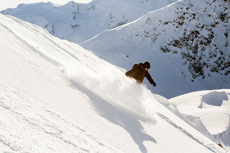 A snowboarder enjoys the powder on a run with Whistler Heli-Skiing