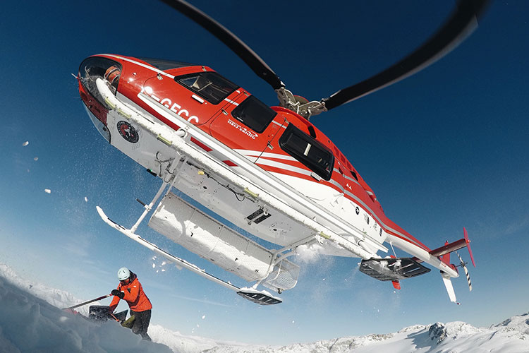 The helicopter lifts off after dropping skiers for Whistler Heli-skiing