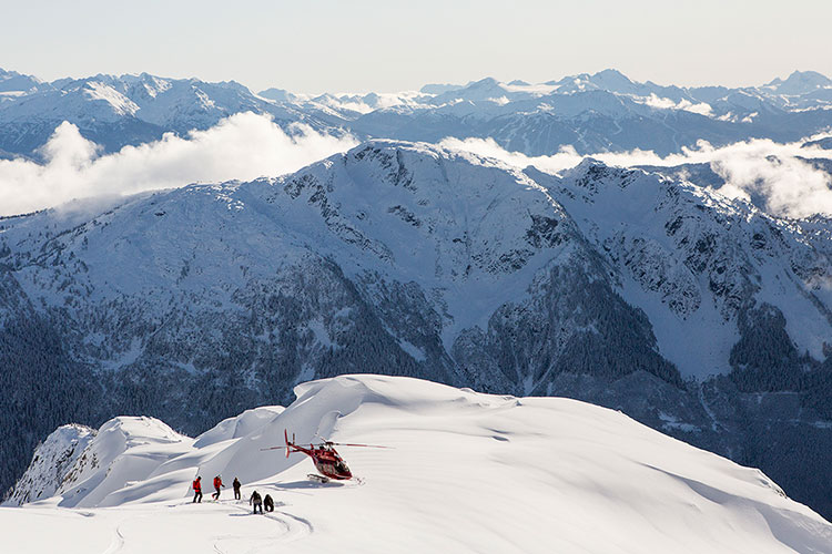 A group of skiers and snowboarders going heli-skiing