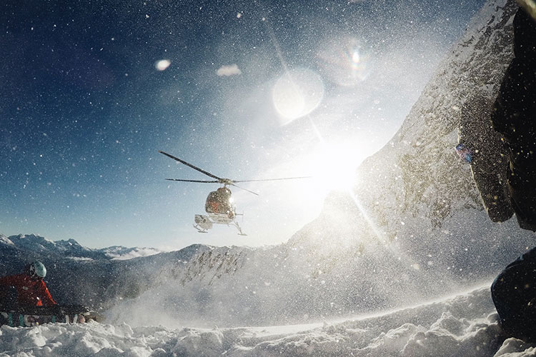 A helicopter takes off after dropping a snowboarder on the mountain in Whistler