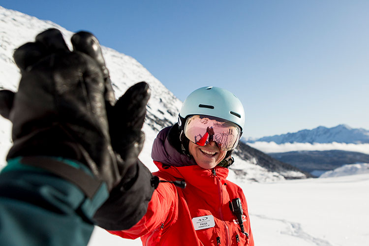 A whistler heli-skiing guide high fives a great slope experience
