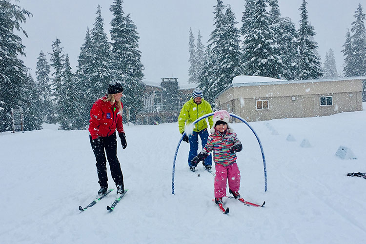 A toddler goes through at hoop while cross country skiing at Whistler Olympic Park.