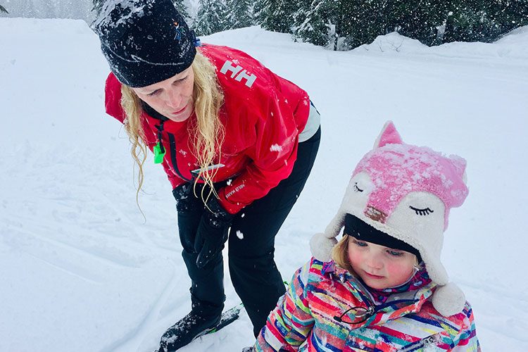 An instructor at Whistler Olympic Park teaching a toddler to cross country ski.
