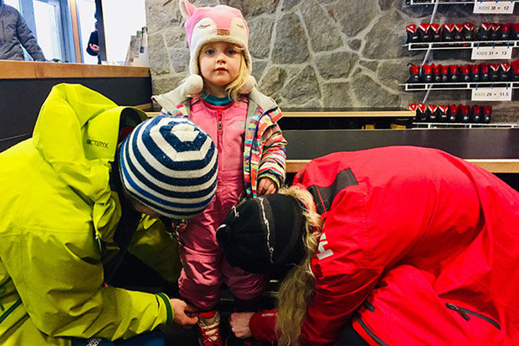 A toddler gets cross country gear on at Whistler Olympic Park.