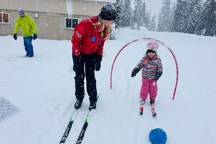 An instructor teaches a toddler how to cross country ski and Whistler Olympic Park.