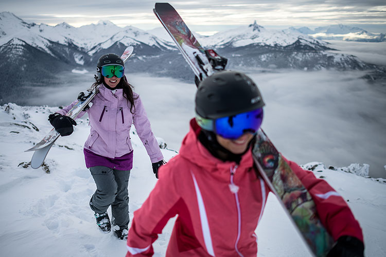 Two teenage girls hike in their ski gear in Whistler.